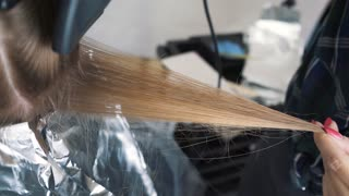 Blowing hair when staining. Drying long brown hair with a hair dryer and a round brush. Close-up.
