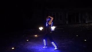 Boy shows different tricks with burning pois rotation at evening fire show.