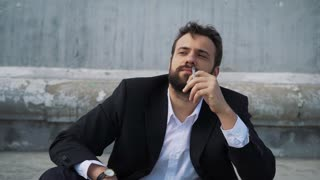 Businessman smoking a cigarette in the city
