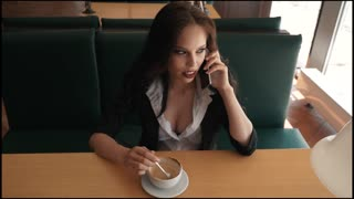 Businesswoman standing at cafe and talking on the phone