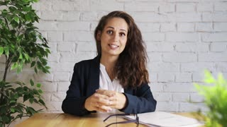 Cheerful businesswoman talking to camera