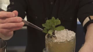 Classy bartender barman serves plain classic rum based drink cocktail lime decoration shaker in bar uniform cruise ship