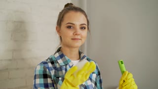 Cleanliness, hygiene, household chores, duties and domestic work concept - beautiful blonde girl blowing foam out of hand. Happy woman in uniform and gloves holds cleanser spray and sponge with foam.