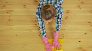 Concentrated woman polishing wooden floor. Young girl in protective gloves washing apartment, spring cleaning concept, copy space