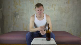 Drunk young man drink a beer at home.
