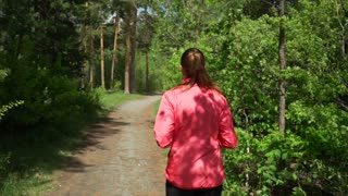 Early Morning Beautiful Girl in Pink Sweater is Jogging in the Woods in Early Spring,on a Background of Trees With Young Leaves,leads an Active Lifestyle