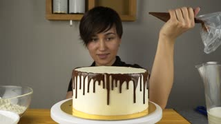 Female chef cook preparing a sweet cake in the kitchen, pouring the chocolate cream on it