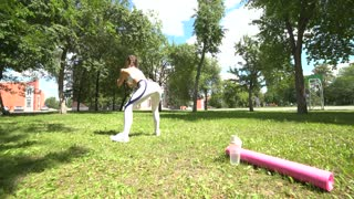 Female fitness trainer doing squat exercises outdoors in park in sunny summer morning