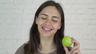 Female with braces on her teeth eating green apple and smile. White. Closeup