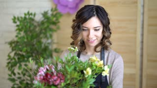 Florist at work: pretty young blond woman holds fashion modern bouquet of different flowers with peone and roses in craft paper