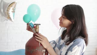 Girl blowing a balloon.