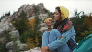 Girl eating hot dog on top of mountain.