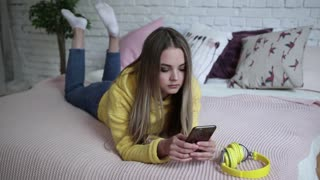 girl listening to music with headphones from phone at home.