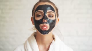 girl with a face mask, inflates bubble gum.