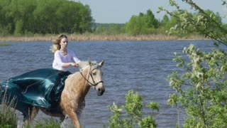 Gray horse jumps in water with woman in slowmotion.