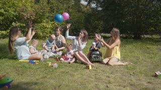 Group of happy children playing outdoors in the summer Park. Mothers look after their children sitting on the grass.