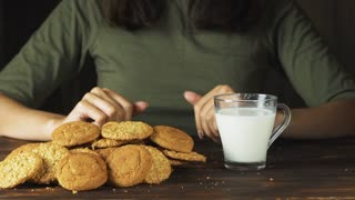 Hand putting a cookie in a glass of milk in slow motion. Food cinematic scene