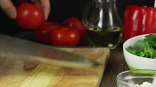 hands slicing tomato in kitchen