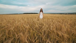 happiness, nature, summer holidays, vacation and people concept - young woman in white dress walking along cereal field