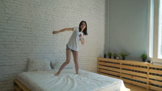 Happy woman jumping and dancing on bed high shot