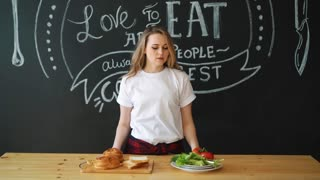 Healthy or harmful food, a girl before choosing a meal