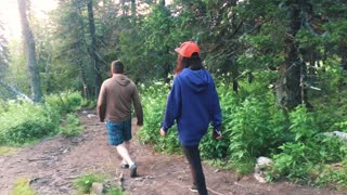 Hiking along the trail on a Sunny day. Group of friends summer adventure travel in mountain nature outdoors