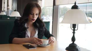 Impatient, young woman looking around and waiting for someone in cafe. Brunette is sitting in a cafe waiting for a meeting