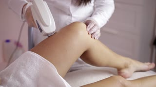 Laser hair removal on ladies legs. The girl is lying on the couch in the medical glasses in the treatment room. The hands of the cosmetologist make the epilation of the legs
