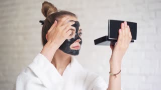 Laughing young girl with a towel on her head puts a black mask on her face, day spa
