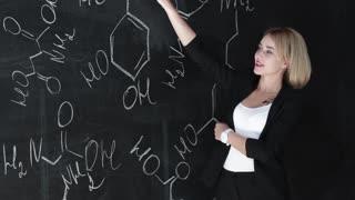 Learn science or chemistry formula confident beautiful woman teacher chalk blackboard background