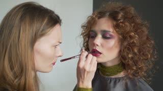 Makeup artist paints lips for girl. Professional make-up of model. Beautiful bride's makeup.