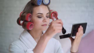Makeup young woman putting lipstick wearing hair rollers getting ready for going out.