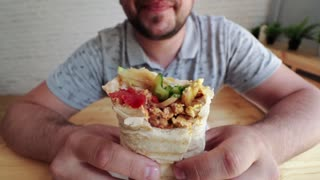 Man eating Doner Kebap its a midlle eastern fast food cuisine