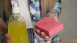 Means for washing dishes, chores casual plaid shirt fabrics people concept. Closeup of a lady cleaning the plates using a viscous detergent. Girl washing dishes. A drop of detergent on the sponge
