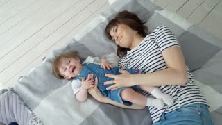Mother and child on a white bed. Mom and baby in playing in sunny bedroom. Parent and little kid relaxing at home. Family having fun together. Bedding and textile for infant nursery