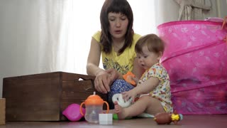 Mum plays with a small child in a room on the floor