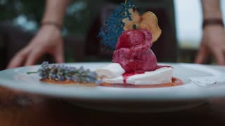 On a clean white table is a plate with a large ice-cream laid out. Form of ice cream in the form of mashed potatoes. Pink color. Rotate the plate. Cold dessert. Fruit ice.