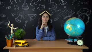 Portrait of a beautiful schoolgirl student , thinking about choosing a profession, on the background of a black Board with a globe . Concept: ideas, school, University, education.