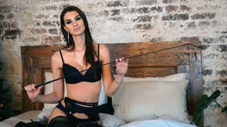 portrait of a fashionable model and comfortable. Beautiful brunette with attractive body in lace lingerie. Girl in black lingerie and a whip.