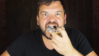 Portrait of a young hungry man eating a donut