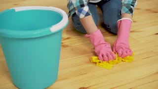 Shocked woman cleaning house with lots of tools. Young tired girl throws a rag in a bucket.