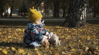 Small child playing in autumn park. Baby playing with yellow leaves. Little girl outdoors in autumn park. Portrait of a baby in autumn park.