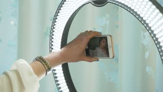 Studio shot of young and beautiful woman taking selfie picture with mobile phone in front of the ring lamp