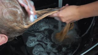 Stylist Sprays Hair With Hose To Rinse Female Customer's Hair at Salon