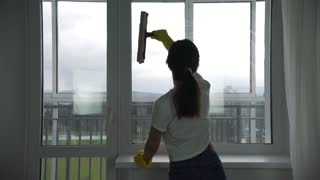 the girl is engaged in washing Windows in the apartment