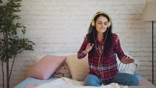 the girl listens to music with headphones and sitting on the bed dancing
