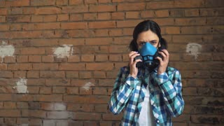 The girl takes off the mask from air pollution. On brick wall background, respiratory mask.
