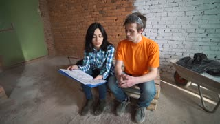 The married couple in the incomplete room looks in the drawing of future house and embrace