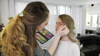 The master in a make-up prepares model for display in beauty shop. The makeup artist professionally does a make-up.