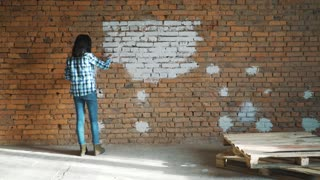 the woman paints a red brick in house in white color